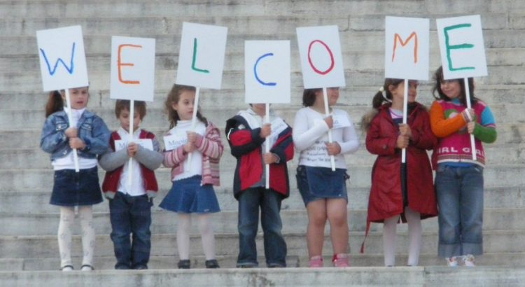 children holding up signs that spell the word WELCOME
